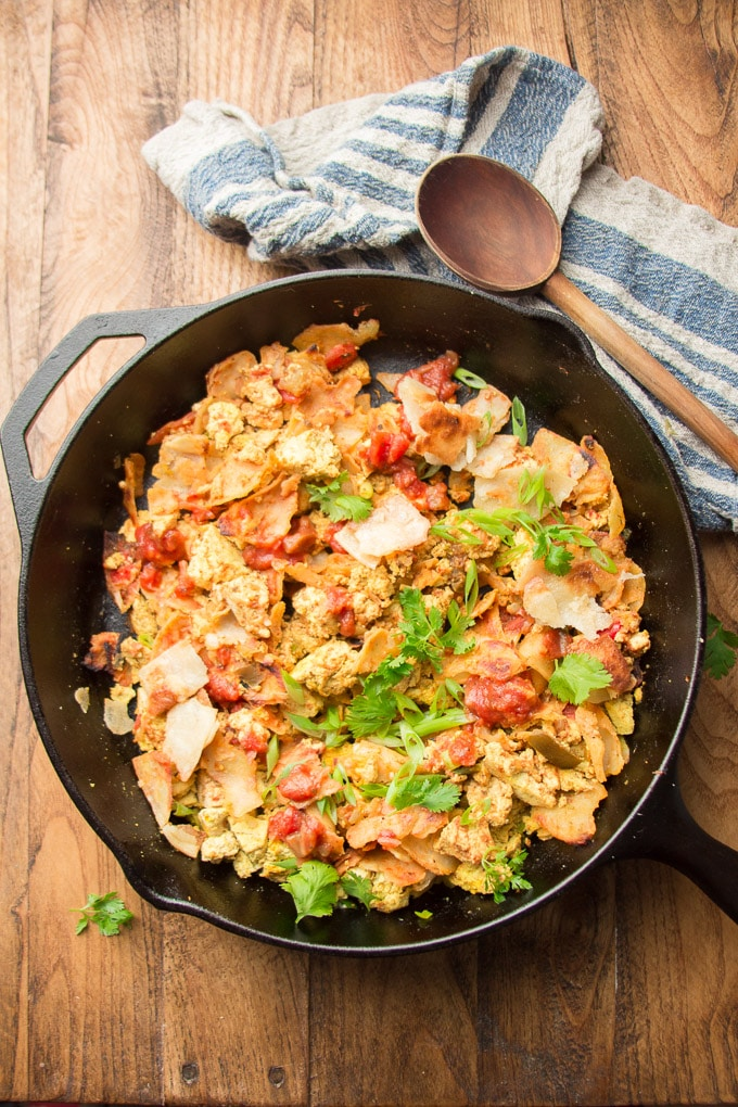 Skillet of Vegan Migas on a Wooden Surface with Napkin and Wooden Spoon
