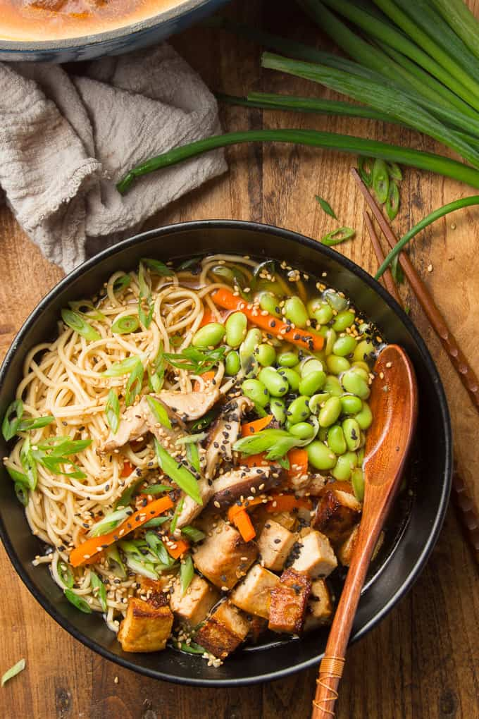 Overhead View of a Bowl of Vegan Ramen on a Wooden Surface with a Wooden Spoon